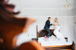Bride and Groom jumping for joy on their wedding day in the bridal suite at Healing manor, lincolnshire wedding photography