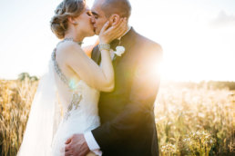 Bride and Groom kissing in a wild flower meadow