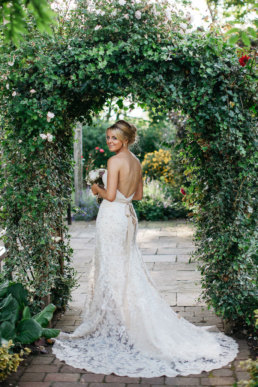 Bride under archway of flowers at a Lincolnshire venue
