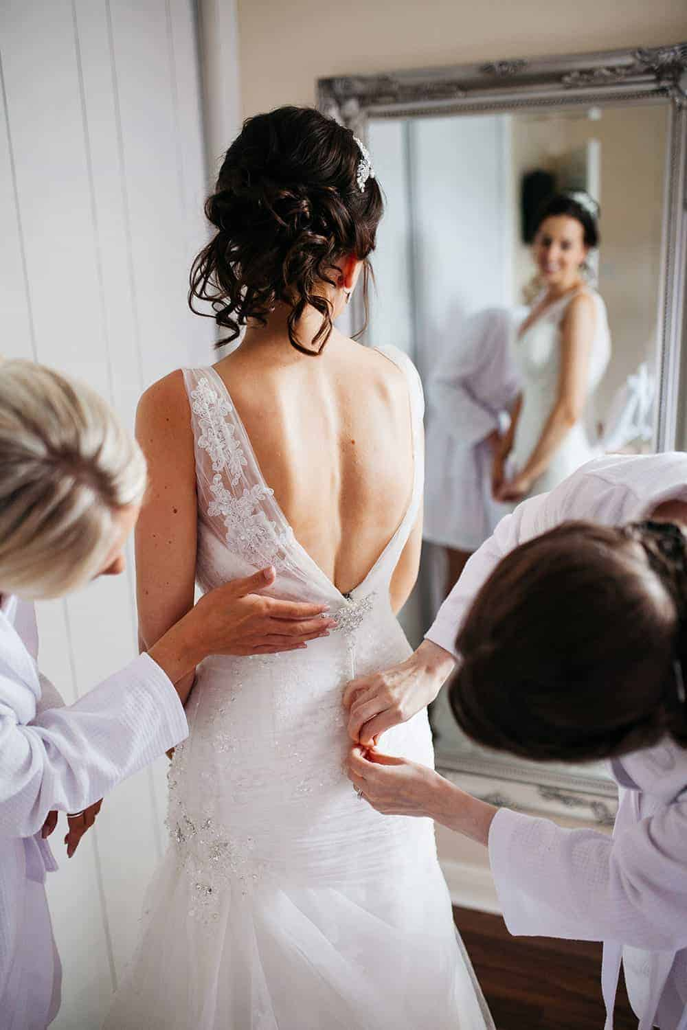 Bride getting help into her wedding dress on the morning of her Lincolnshire wedding