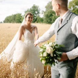 Couple walking through a farmers field at their wedding at Hirst Priory